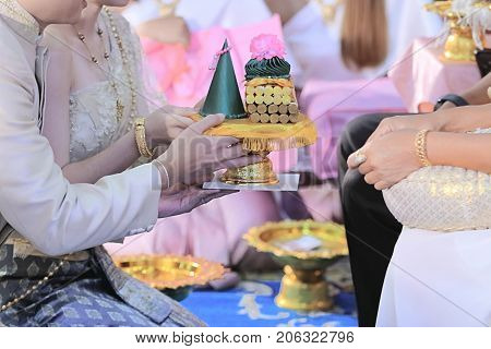 Groom and bride offering tray of gift to older in traditional Thai wedding ceremony. Concept of marriage.