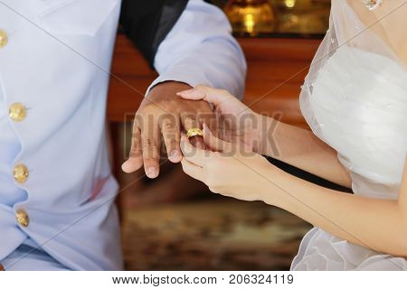 Bride newlyweds wearing ring on groom's finger in wedding ceremony.