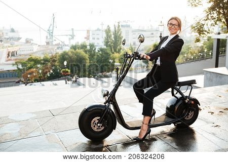Full length Side view image of happy business woman sitting on modern motorbike outdoors and looking at the camera