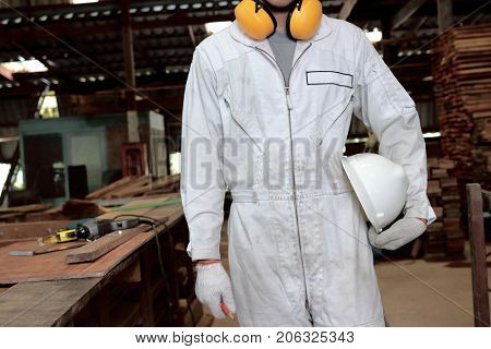 Portrait of young worker in white uniform holding safety helmet in carpentry workshop.