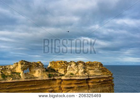 Cliff With Ocean And Overcast Sky On The Background