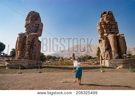 The girl near the beautiful ruins of ancient statues in Luxor, Egypt