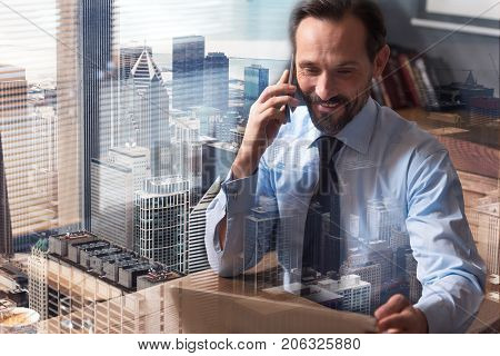 Business talk. Positive confident sucessful businessman sitting at the table and talking on phone while working in the office