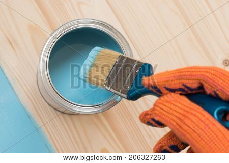 worker paints board. the employee paints the a wooden table. worker paints wooden board. brush in hand. hand in gloves. House renovation, paint can on the old wooden background with copy space