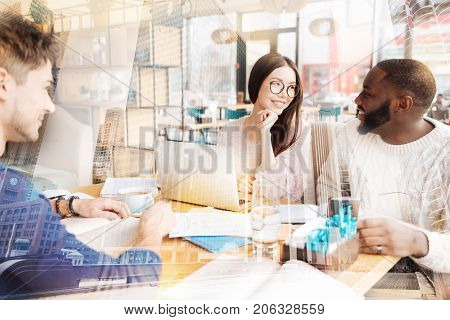 Being in love. Young optimistic couple sitting at the table and looking at each other while their friend observing them with admiration