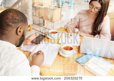 Concentrated on studying. Close up of diligent attentive students preparing for significant test while drinking tasty tea