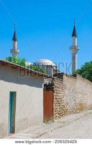 Mosque Han-Jami, city Yevpatoriya, Crimea , among green trees, against the sky