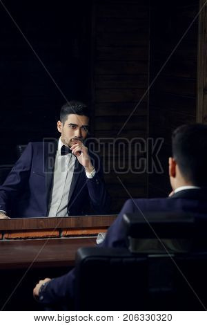 Confident man in blue suit and butterfly sitting in chair looking in the mirror in barbershop.