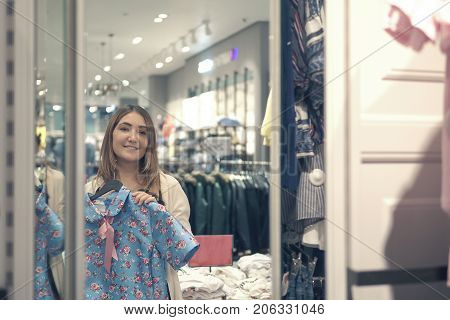 Yong girl choosing clothes and looking to mirror in mall or clothing store. shopping fashion style and people concept.