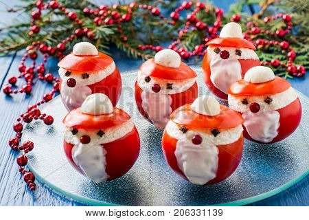 Idea for Christmas party: funny Santa Claus from tomatoes. Tomatoes stuffed with cheese and garlic on plate. Original snack with Christmas and New Year. Blue wood background with Christmas decorations