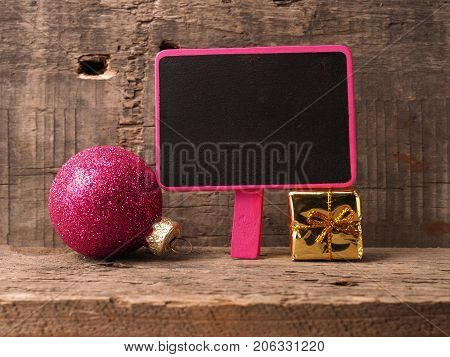 Small chalkboartd with an old Christmas bauble and gift box on a rustic wooden background