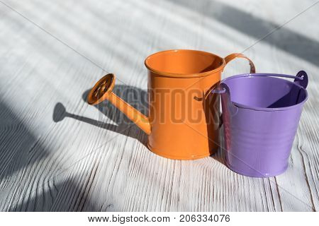 Orange Purple Watering Can And A Bucket Standing On Wooden Background.
