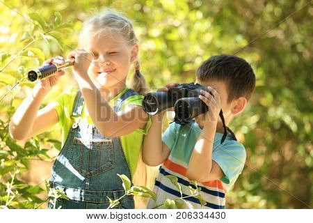 Cute children with binoculars and spyglass outdoors