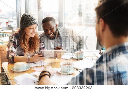 Exciting video. Smiling concentrated friends holding a tablet while looking at the screen with excitement