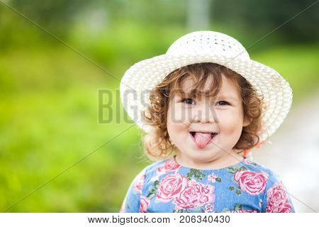 Funny curly blond toddler girl smiles and teases.