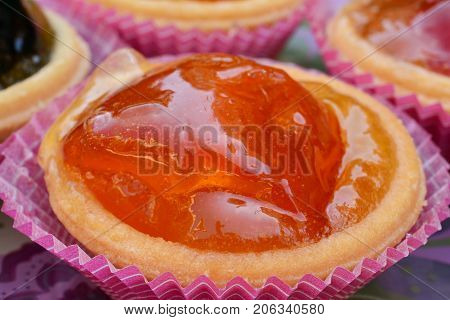 Traditional Greek sweet candied orange in punnet of dough close up view