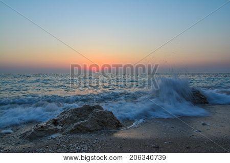 Sunset on a beach splashing waves sand rocks and sun on horizon in twillight