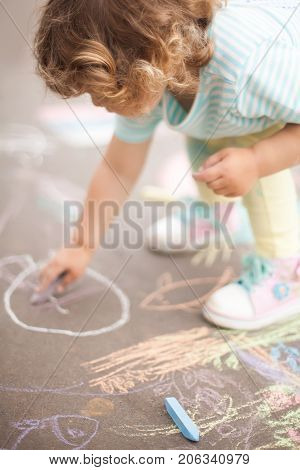 Sunny and warm summer days and happy chilhood. Cute little girl drawing with chalk crayons at the asphalt.