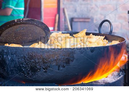 Cooking and deep frying in fatiscent big pan or wok street food stall in India junk unhealthy eating. Fire coming out below the pan.