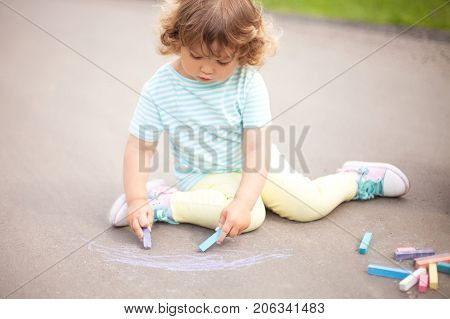 Sunny and warm summer days and happy chilhood. Cute little girl drawing with chalk crayons at the asphalt. Empty place fot text copyspace. Child having fun alone. Spending time without parents and adults.
