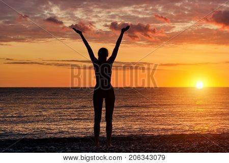 Girl Standing Hands Up On The Beach At Sunset. Silhouette
