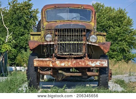 Front part of an old-fashioned rotting truck in the yard