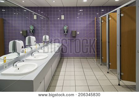 Cardiff, UK: November 13, 2016: Public bathroom. Ladies restroom with cubicles and sinks and a purple tiled wall.