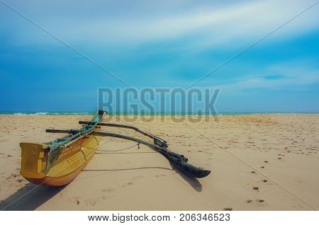 Beach and tropical sea.Fishing boat. Paradise idyllic beach Sri Lanka. Beautiful Sri Lanka landscape. Exotic water landscape with clouds on horizon. Summer holidays. Ocean shore in the evening as nature travel background.