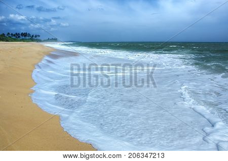 Wave of the sea on the sand beach.Beach and tropical sea. Paradise idyllic beach Sri Lanka. Beautiful Sri Lanka landscape. Exotic water landscape with clouds on horizon. Summer holidays. Ocean shore in the evening as nature travel background.