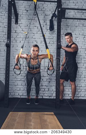 Woman Exercising With Trx Gym Equipment