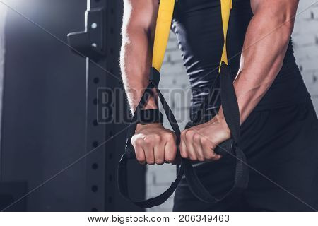 cropped shot of man exercising with trx gym equipment