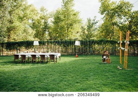 Wedding decorations for the ceremony outside in sunny weather in a beautiful garden. Beautiful wedding archway with chairs on on each side for the guest on the wedding ceremony.