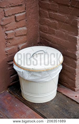 White Zinc bucket bin with lid and plastic bag inside in the corner.