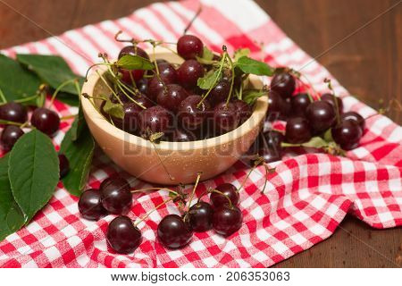 cherry in a wooden bowl on a napkin