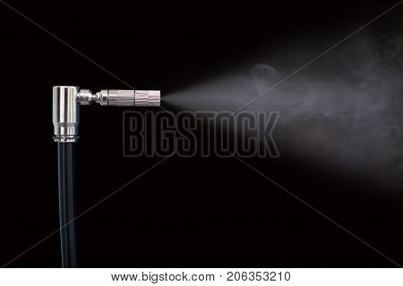 The nozzle sprays liquid into vapor. Close up of a spray drops on black background