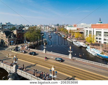 Amsterdam Netherlands - September 24 2017: Some tourists are walking on the bridge against the background of the Dutch National Opera and Ballet aerial view