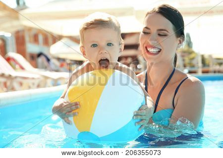 Mother and baby with inflatable ball in swimming pool