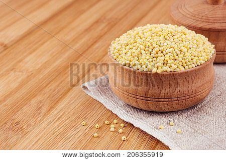 Millet in wooden bowl on brown bamboo board closeup. Rustic style healthy dietary groats background.