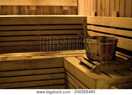 sauna bucket in wooden sauna room. Wooden sauna room in low light. For relaxation time.
