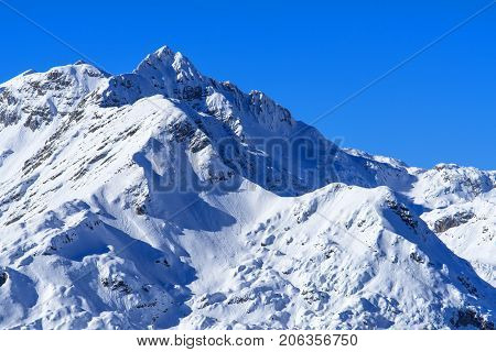 Beautiful mountain peaks under snow against clear blue sky as copy space part of Julian alps mountain range