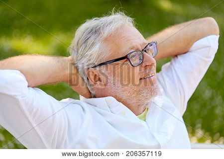 old age, retirement and people concept - happy senior man in glasses sitting and relaxing outdoors