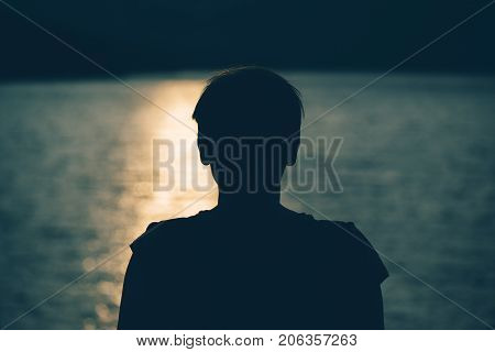 Silhouette of depressed sad woman standing by the lake in cold autumn sunset. Gloomy adult female person looking at water. Loneliness and solitude concept.