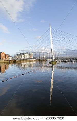 Swansea, UK: February 08, 2017: Footbridge over the River Tawe at the Swansea Marina. Sailboats moored in the marina.