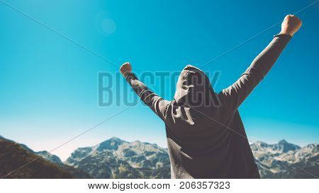 Winning and success. Victorious female person standing on mountain top with arms raised in V. Achievement and accomplishment in life. Toned image.