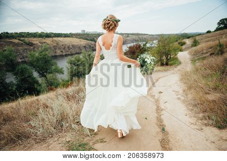 Beautiful bride walk down the aisle with bouquet. Unrecognizable woman in wedding dress going with flowers to bride, close-up
