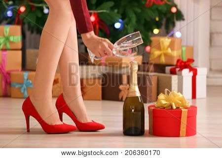 Woman in high heel shoes holding glasses for champagne at home