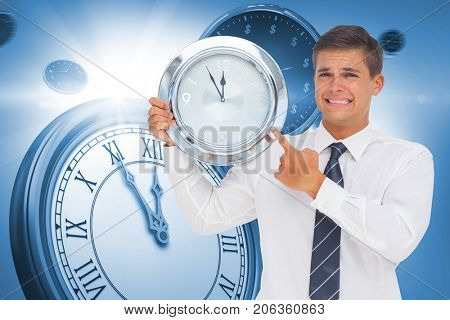 Anxious businessman holding and showing a clock against computer generated image of clocks
