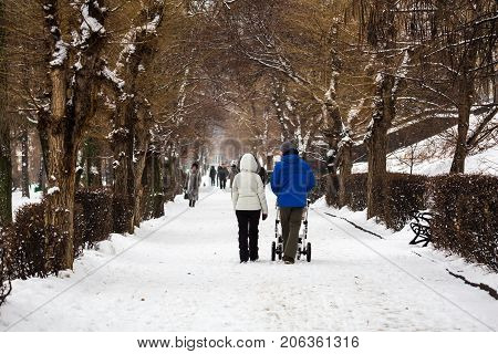 City Park in winter. A young family walks. Mom, dad and a stroller with a small child.