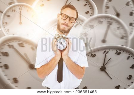 Geeky businessman holding alarm clock against digital image of wall clocks