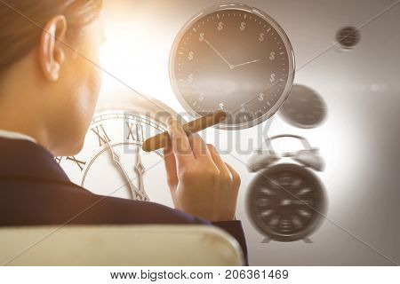 Businesswoman holding cigar against computer generated image of clocks